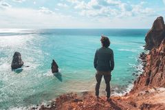 Man traveler over cold sea landscape. Back view of man traveler standing on mountain alone and looking at autumn sea landscape. Hiking in cold season. Wanderlust Stock Images