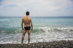 Back view of man in trunks against of seascape. Back view of sexy unrecognizable man in trunks on beach against of sea Royalty Free Stock Photos