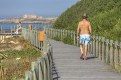 10 04 2018: Back view at a man, walking on the eco pedestrian path, near the sea, Portugal stock image