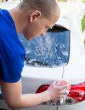 Back view of man washing rear lights of car with sponge. And soap Stock Image