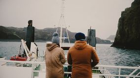 Back view of man and woman standing on ship and enjoying beautiful landscape, talking. Tourists exploring Iceland. stock video