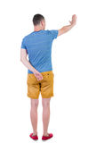 Back view of man. Young man in shorts presses down on something Royalty Free Stock Photos