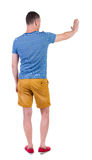 Back view of man. Young man in shorts presses down on something Stock Image