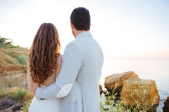 Back view of a married couple hugging on the beach. Back view of a romantic married couple hugging on the beach at sunset Royalty Free Stock Photos