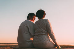 Back view a married couple a silhouette sitting on a bench. Royalty Free Stock Photography