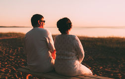 Back view a married couple a silhouette sitting on a bench. Royalty Free Stock Images