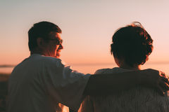 Back view a married couple a silhouette sitting on a bench. Stock Photos