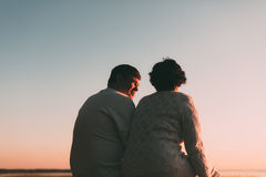 Back view a married couple a silhouette sitting on a bench. Stock Photography