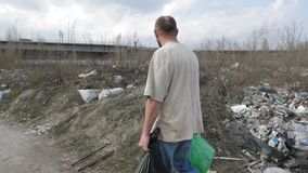 Man walking along garbage dump with trash bins. Back view of mature homeless man in dirty t-shirt and jeans walking along garbage dump in city with trash bins stock video