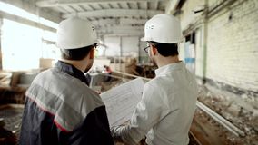 Back view of men in helmets and eyeglasses standing together in construction area with people in the background. Back view of two men in white safety helmets and stock video footage