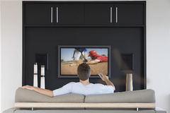 Back view of mid-adult man changing channels with television remote control in living room Stock Images