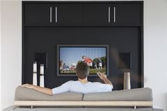 Back view of mid-adult man changing channels with television remote control in living room royalty free stock photography