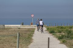 Back view of middle-aged couple, cycling on the eco pedestrian / bike path, near the sea. Portugal royalty free stock photo