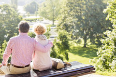 Back view of middle-aged couple relaxing on park bench royalty free stock photo