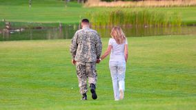 Back view military man on date in a park lawn. Happy soldier with woman on glade, rear view stock footage