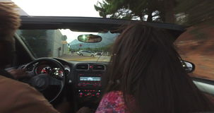 Back view of mixed race couple driving in convertible. At dusk stock video footage