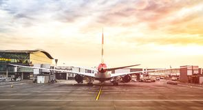 Back view of modern airplane at terminal gate ready for takeoff. On runway - International airport with cloudy sky - Travel and wanderlust concept around the stock images