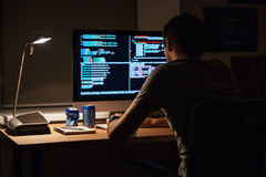 Back view of modern programmer sitting and writing code Royalty Free Stock Photography