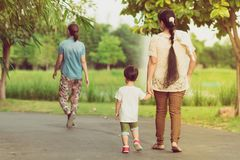 Back view of mom and son walk for excercise together before sunset stock image