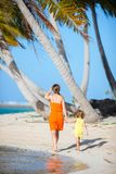 Mother and daughter on tropical vacation. Back view of mother and daughter on a deserted island stock photo