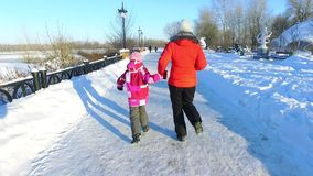 Back view mother and daughter running in winter park. Happy wintertime. Back view mother and daughter running in winter park. Family fun on snow pathway stock video footage