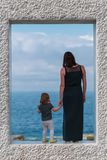 Back view on mother with daughter who stay on marble frame and looking at the sea stock images