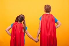 Back view of mother and her little girl dressed like superheros holding hands.