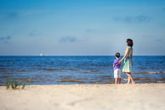 Back view of mother and her son at summer beach Royalty Free Stock Images