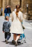 Mother and two kids walking in city center. Back view of mother with her son and toddler daughter in stroller walking in city street in Malta Europe royalty free stock images