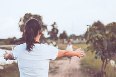 Back view of mother raise hand to wait her child girl. Running to give a hug with love in the park in vintage color tone Royalty Free Stock Photography