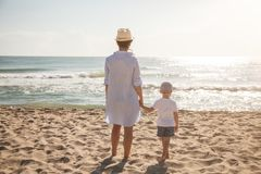 Back view of mother and son on the beach at sunny day. Family vacation. On summer stock photography