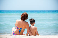 Back view of mother and son sitting on tropical beach Royalty Free Stock Image