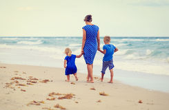 Back view of mother and two kids walking on the beach. Back view of mother and two kids walking on summer beach Stock Images