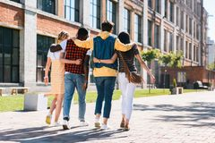 Back view of multicultural group of friends hugging while walking. On street together royalty free stock images