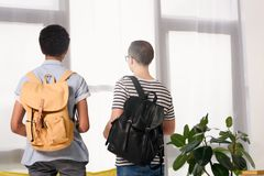 Back view of multicultural teen boys standing with bags at home stock image