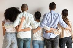 Back view of multiracial friends hug showing unity and support