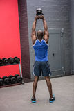 Back view of muscular man lifting a kettlebell Stock Photo
