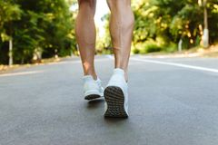 Back view of muscular sportsman legs running. On the road outdoors Royalty Free Stock Photos