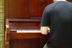 Back view of music performer playing piano. At luxury hotel Royalty Free Stock Photography
