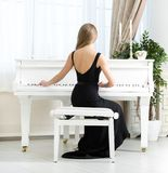 Back view of musician sitting and playing piano Stock Images
