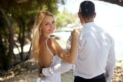 Back view of newly married hug each other on tropical island beach on Maldives. Bride turns around and looks to camera stock photography