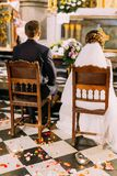Back view of the newlyweds sitting on the chairs during the wedding ceremony in the church. Royalty Free Stock Images