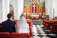 Back view of the newlyweds sitting on red chairs of church, selective focus royalty free stock photos