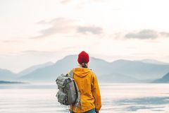 Free Back View Of Male Tourist With Rucksack Standing On Coast In Front Of Great Mountain While Journey Royalty Free Stock Photos - 162222468