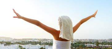 Free Back View Of Pretty Girl On A Balcony Wrapped In White Towel After Having A Bath. Woman Is Enjoying A Mountain View And The Sunset Stock Photo - 190777580