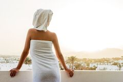 Free Back View Of Pretty Girl On A Balcony Wrapped In White Towel After Having A Bath. Woman Is Enjoying A Mountain View And The Sunset Royalty Free Stock Images - 190777849