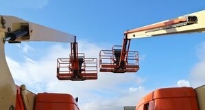 Free Back View Of Two Aerial Work Platforms Against Blue Sky With Clouds. Stock Photo - 206645500