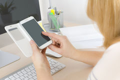Back view of office worker touching smart phone with finger Royalty Free Stock Photo