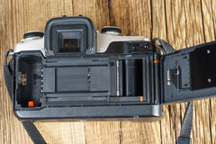 The back view of an old film camera wooden background. The back view of an old and dusty film camera Stock Photo