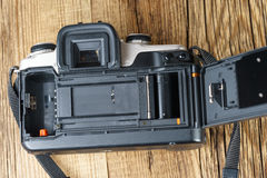 The back view of an old film camera wooden background. The back view of an old and dusty film camera Royalty Free Stock Photo